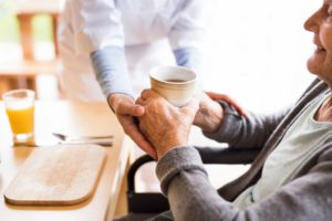 assisted living caregiver helping resident with their beverage